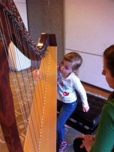 Girl playing the harp at the LPO Funharmonics 2015