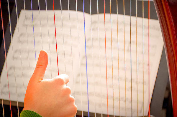 Hand on the strings of a lever harp with harp music in the background