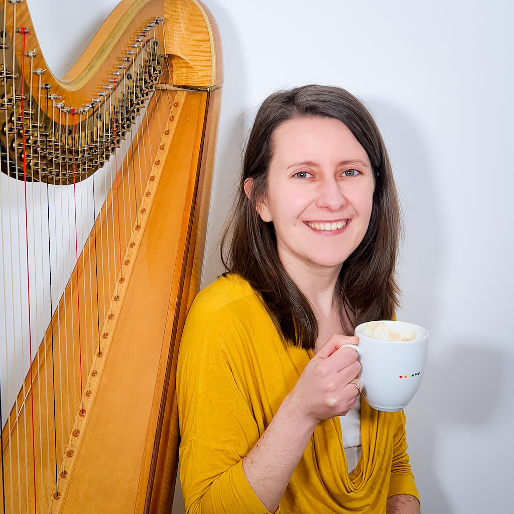 Zuzanna next to her harp, holding a cup of coffee